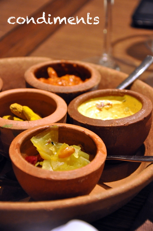 the condiments served in an earthen tray. the raw papaya relish (which was outstanding), hung curd dip, lemon pickle, coriander chutney with pomegranate seeds and turmeric