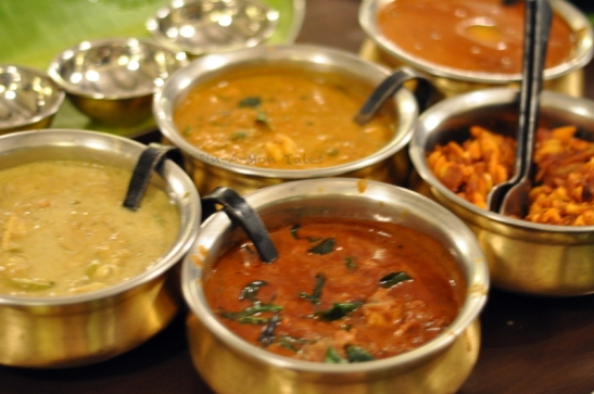 The curries - Koorka Chemmen Peralan (koorka, baby potatoes, and medium prawn cooked in spiced coconut milk Meen moilee - Fish cooked with mild spices in coconut milk  Kozhi Varatharachathu - Spiced chicken with broiled coconut  Chakka Kuru Kashvandi Ularthu - Jackfruit seeds and tender cashew cooked dry  Kadachakka Theeyal - Bread fruit cooked in roasted coconut, jaggery and tamarind